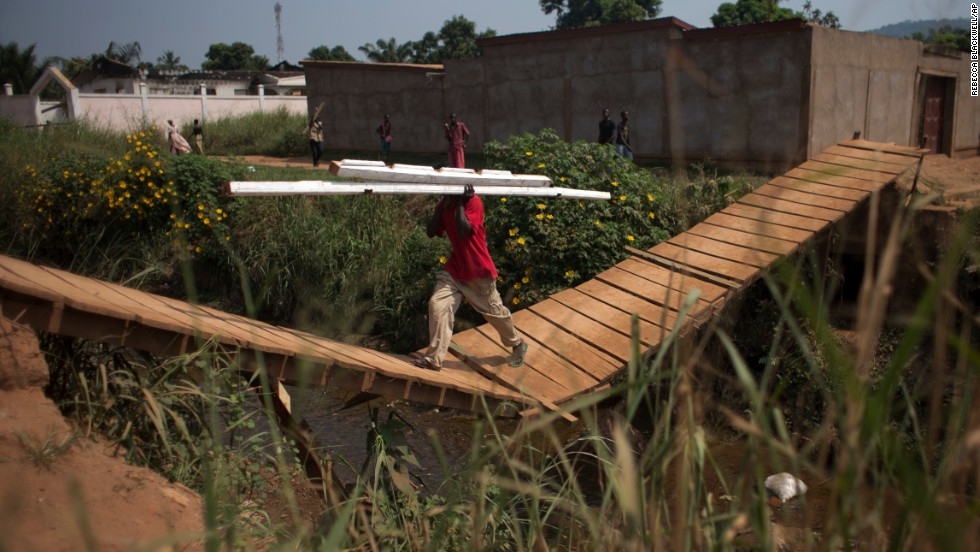 A man carries beams stripped from a Bangui house, back left, which is said to have belonged to a Seleka officer who had been attacking the surrounding Christian population.