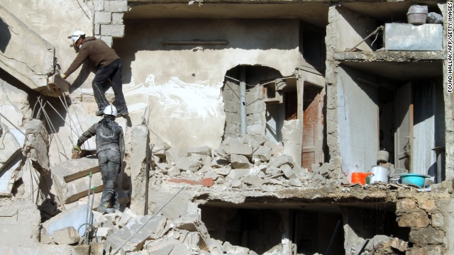 Rescues climb on the rubble of a destroyed building following an airstrike in  Aleppo on December 24.