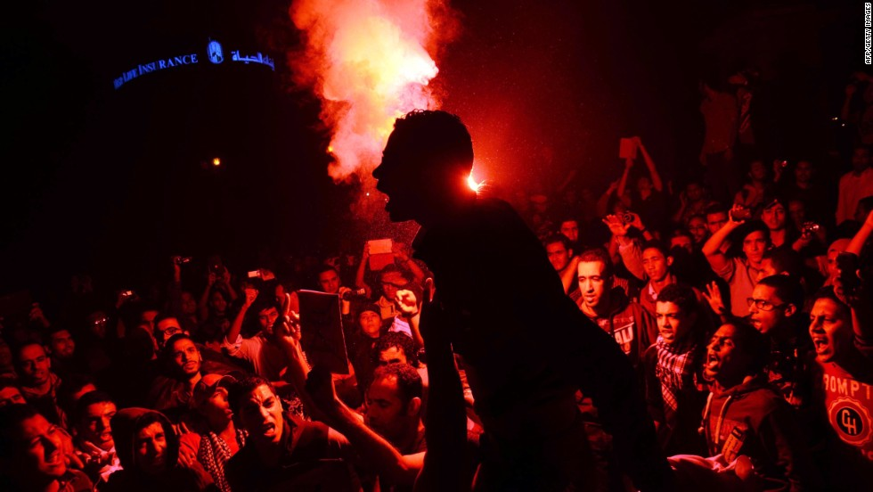 "Egyptian protesters use flare lights at Talaat Harb Square in downtown Cairo on November 26, 2013 during a clash with police after the security forces dispersed protesters from a demonstration organized by human rights group ""No Military Trials for Civilians"" in the first unauthorized protest staged in the capital since the adoption of a law that regulates demonstrations."