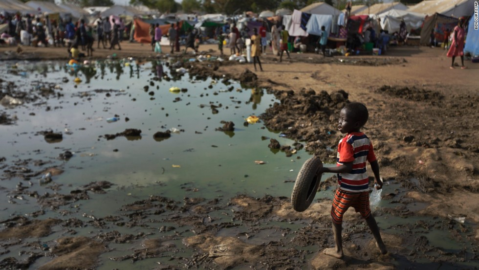 A child plays with a tire next to a large puddle of muddy water inside the U.N. compound in Juba on December 29.