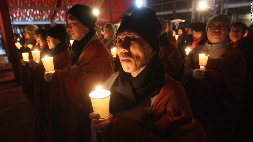 Buddhist monks hold candles during celebrations at a temple in Seoul, South Korea.