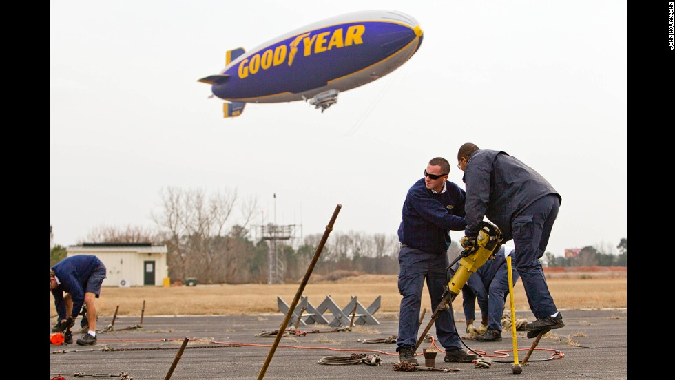 The Goodyear blimp Spirit of Innovation arrived in Atlanta on December 30 to prepare for its New Year's Eve flight above the Chick-fil-A Bowl. Aaron Hullander, left, and Olenskian Spoon carry a jackhammer to secure posts as the Goodyear Blimp comes in for a landing at DeKalb-Peachtree Airport.