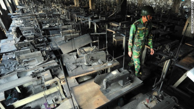 A Bangladeshi Army personel walks through rows of burnt sewing machines after a fire in the plant.