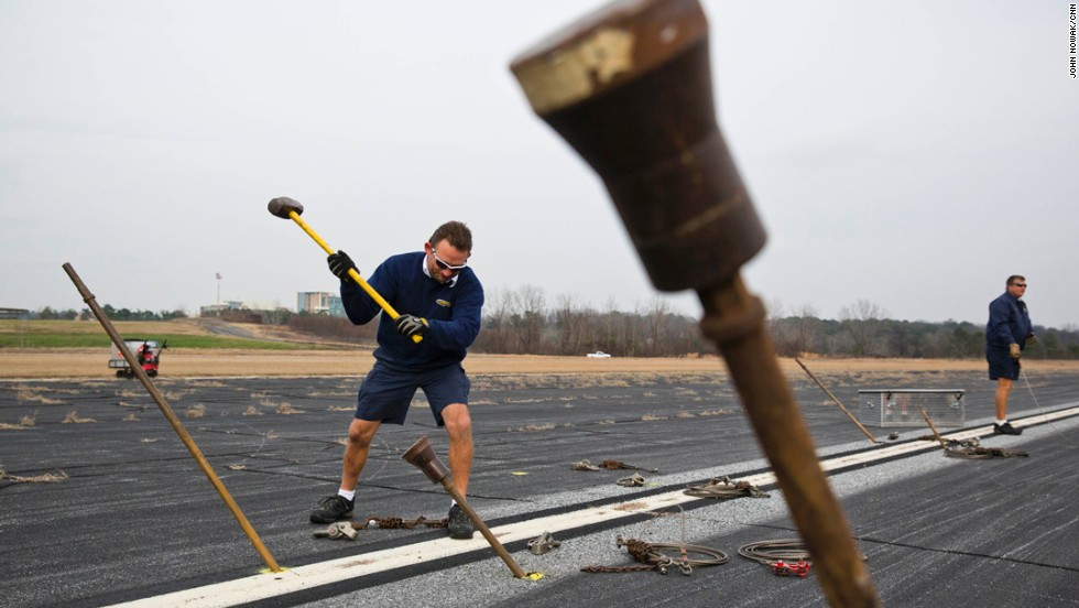 Scott Suter, an airframe and power plant mechanic, uses a sledgehammer to secure support posts into the runway. Suter is one of the ground crew members for Spirit of Innovation, which is based in Pompano Beach, Florida.