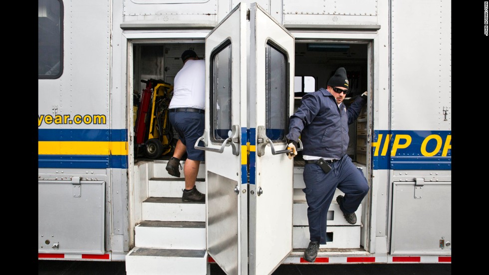 Ground crew members enter and exit one of the trucks that accompanies the Goodyear blimp before it lands at DeKalb-Peachtree Airport.