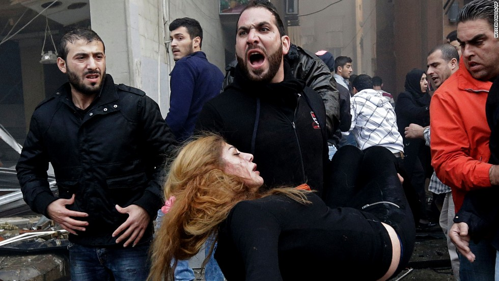 A man carries an injured woman away from the site of a car bomb explosion in Beirut, Lebanon, on Thursday, January 2. The bomb went off in a residential neighborhood of southern Beirut.