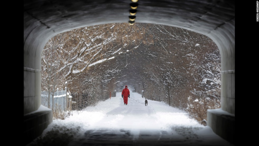 A man walks his dog on the snow-covered Monon Trail in Carmel, Indiana, on January 2.