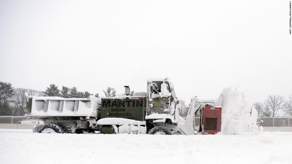 A truck-mounted snowblower clears a section of road in Dedham, Massachusetts, on January 3.
