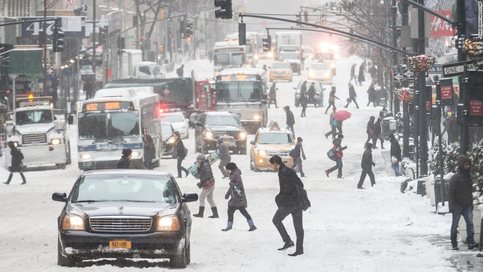 Pedestrians brave wind and snow as they cross New York City's Fifth Avenue on January 3.