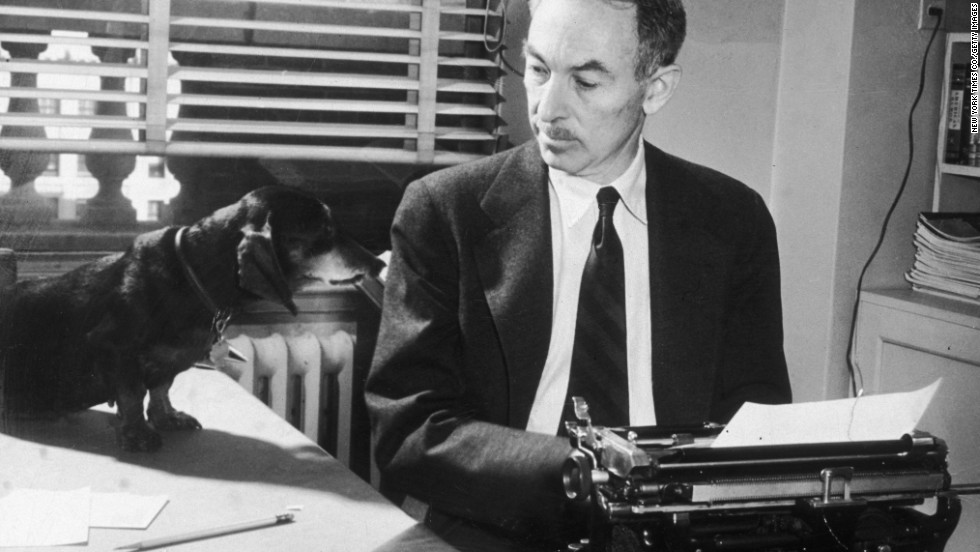 Writer E.B. White looks at his pet dachshund, Minnie, while typing in his office at The New Yorker magazine circa 1948.