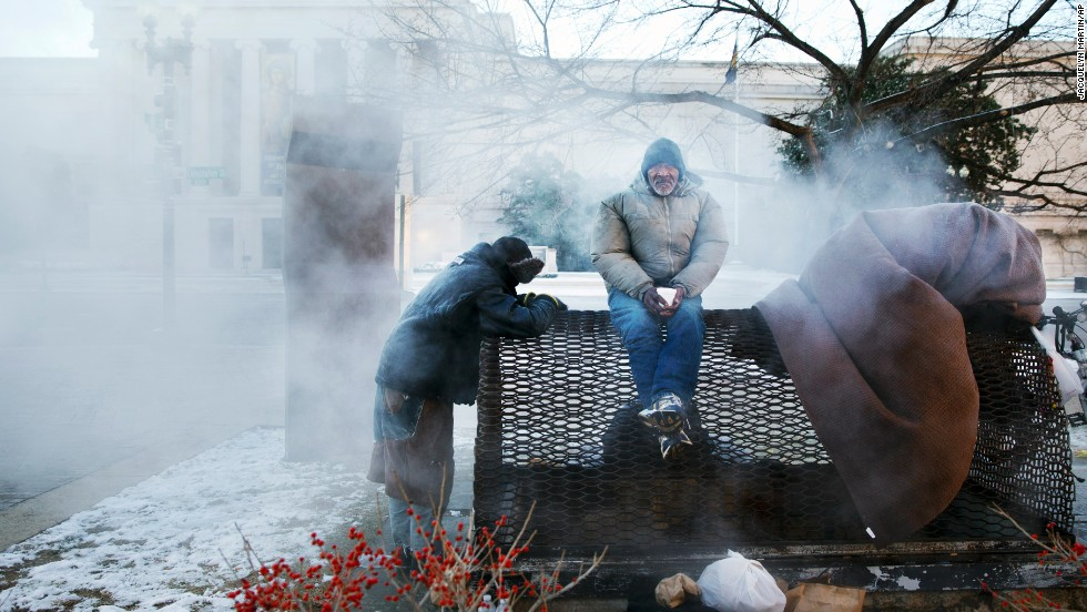 Four homeless men warm themselves on a steam grate by the Federal Trade Commission Building, blocks from the U.S. Capitol in Washington, as frigid temperatures grip the nation's capital on Saturday, January 4.