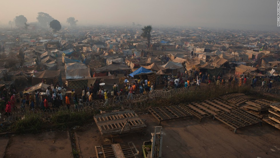 Displaced people walk amid makeshift shelters at a camp abutting M'Poko International Airport on January 4.