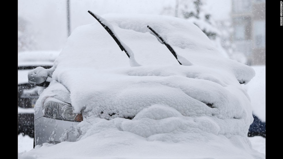 A car is buried in snow January 5 in Zionsville, Indiana.