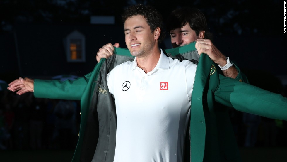 Bubba Watson helps Scott don the green jacket at the 2013 Masters after the Australian won his first major after a playoff with Angel Cabrera.