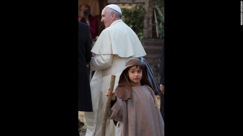 A child participating in the nativity scene stands next to Pope Francis.