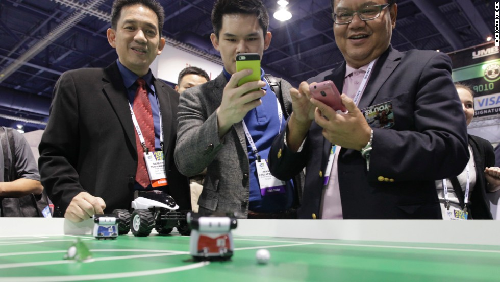 CES attendees use their phones to control BeeWi's Bluetooth Athlete Robots and play a game of table soccer.