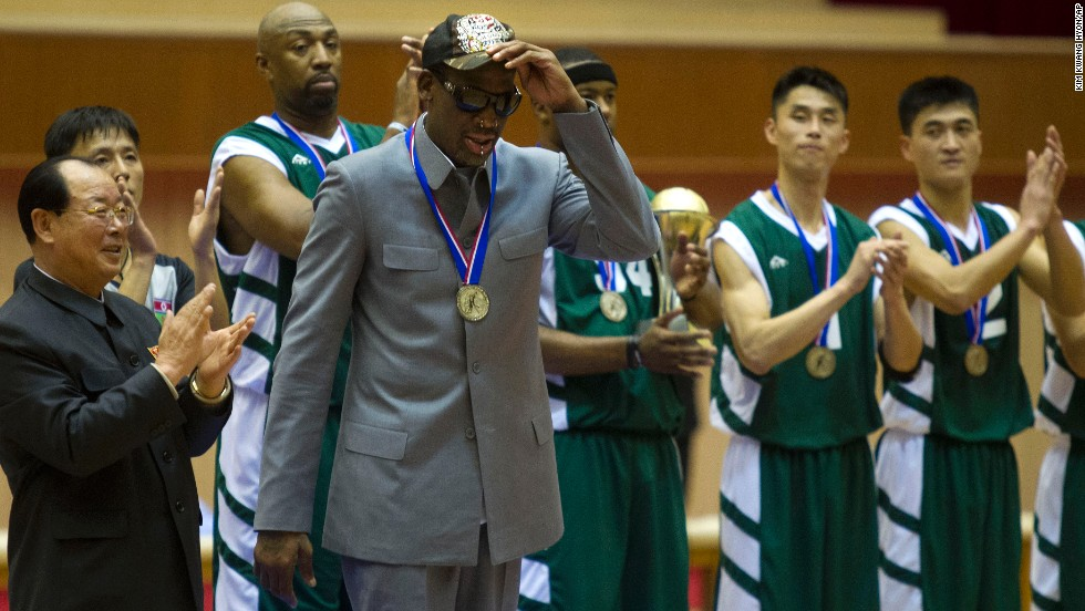 Rodman tips his hat as U.S. and North Korean basketball players applaud at the end of the game.