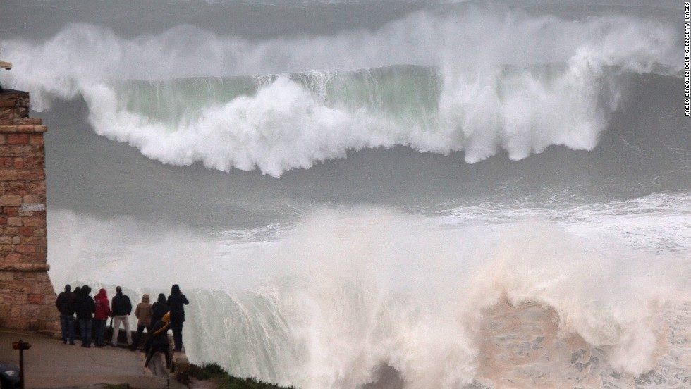 Last year surfing hot spot Praia do Norte in Nazare, Portugal was also graced by mighty waves but this crowd sensibly decided to stay on the shore as the surf broke.