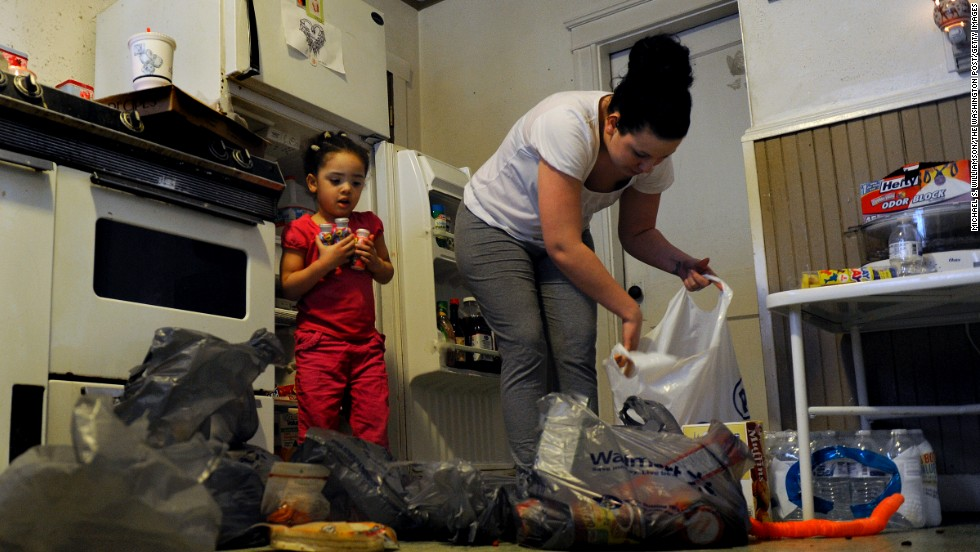 A mother unloads groceries purchased with food stamps in 2013. The federal food assistance program established by President Johnson in 1964 still helps many low-income Americans put food on the table today.