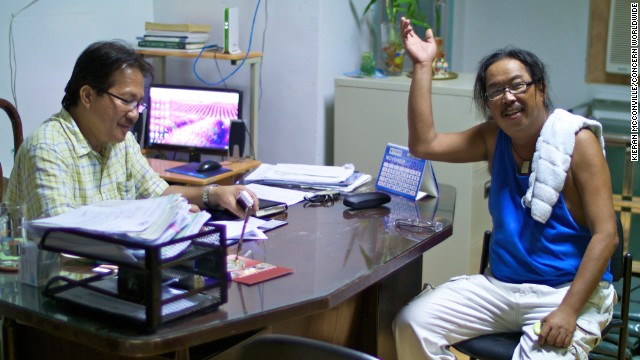 Leo Ladaquin waves a greeting from the mayor's office in Concepcion. On the left is Mayor Villanueva.