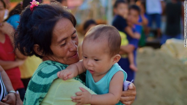 Rowena Costorio and her son Crisantos wait in line for relief supplies.