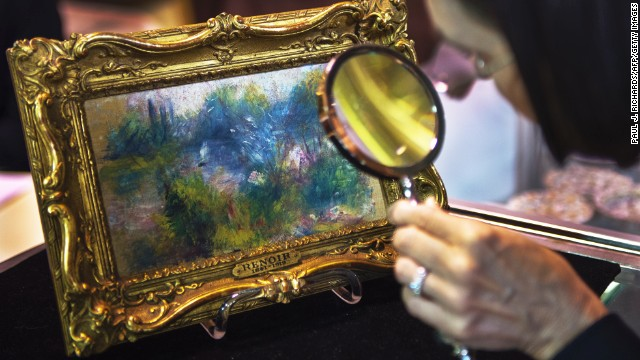 An art lover examines the tiny work by Renoir