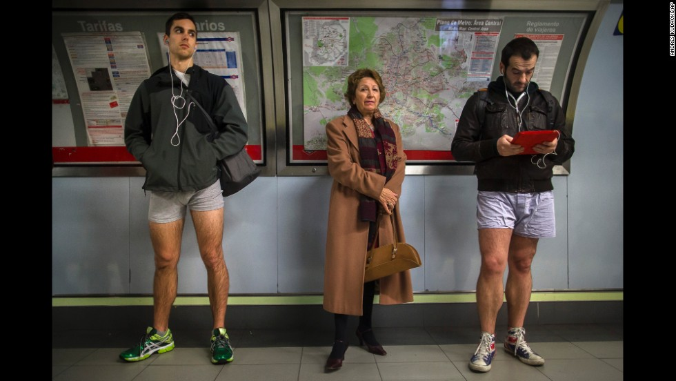 A woman stands between two pantsless passengers in Madrid.