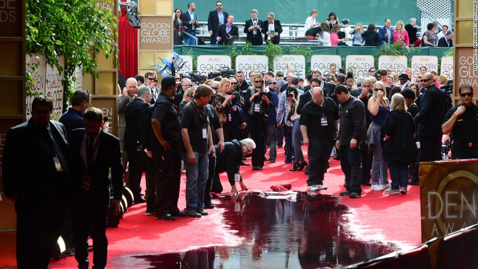 Staff clean up after a sprinkler malfunction dumped water on the red carpet before the start of the event.
