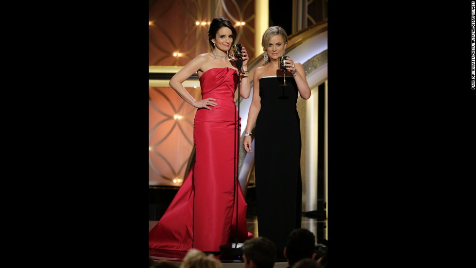 Fey and Poehler take the stage with glasses of wine.