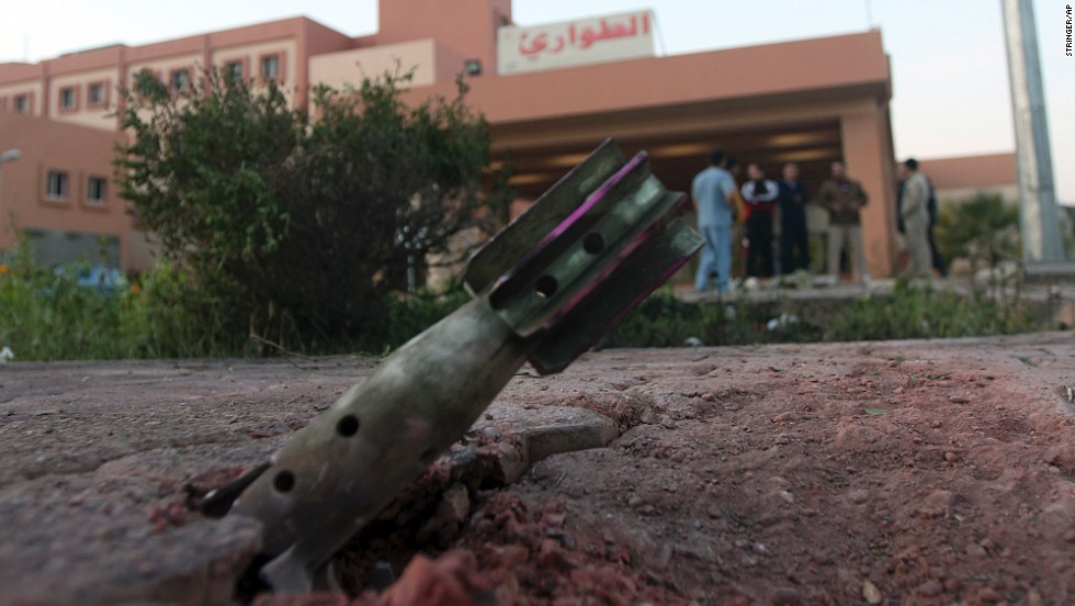 People gather near an unexploded mortar shell in front of a hospital in Falluja on Monday, January 13.