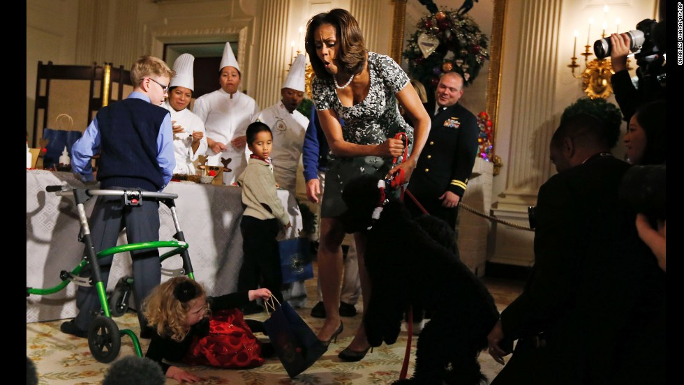Michelle Obama reacts as Ashtyn Gardner, a 2-year-old from Mobile, Alabama, loses her balance while greeting Sunny, one of the Obamas' dogs, at a White House event in December.