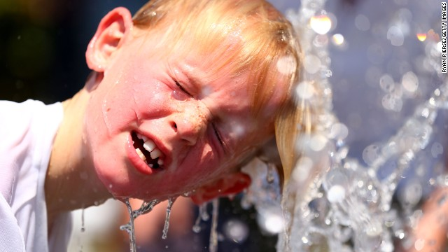 A child plays in the water fountain in the heat during day four of the 2014 Australian Open in Melbourne.