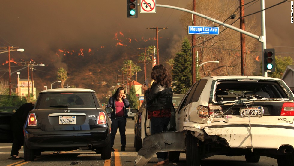 Motorists exchange information after a car accident while the wildfire burns in the Glendora hills on January 16.