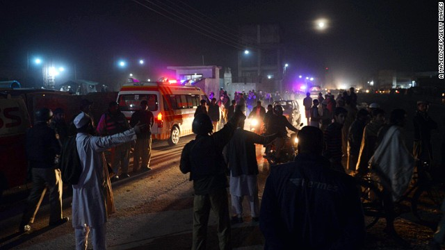 Pakistani policemen and Islamists gather outside a preaching center after a bomb explosion in Peshawar on Thursday.