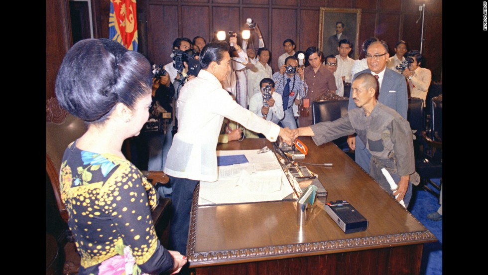 Philippine President Ferdinand Marcos, left, greets Onoda at Malacanang Palace in Manila under the watchful eye of first lady Imelda Marcos in March 1974. Nearly three decades after World War II's end, Onoda was persuaded to come out of hiding after his former commanding officer traveled to Lubang and told him he was released from his military duties.