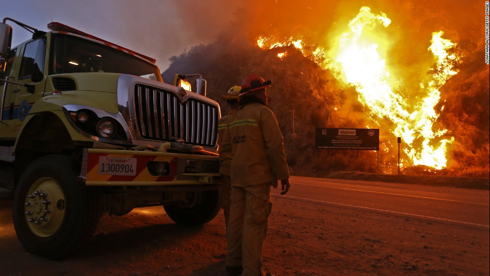 Firefighters watch the Colby Fire on January 17. The blaze began before dawn Thursday, January 16, and allegedly originated with three men camping in the foothills near Glendora, California, authorities said.