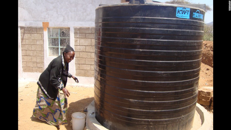 A woman draws water from a collection tank. Borrowers in Kenya are using WaterCredit loans to purchase large water storage tanks. These water tanks provide additional income to families, who sell the water to neighbors or irrigate gardens and fields for better crops.