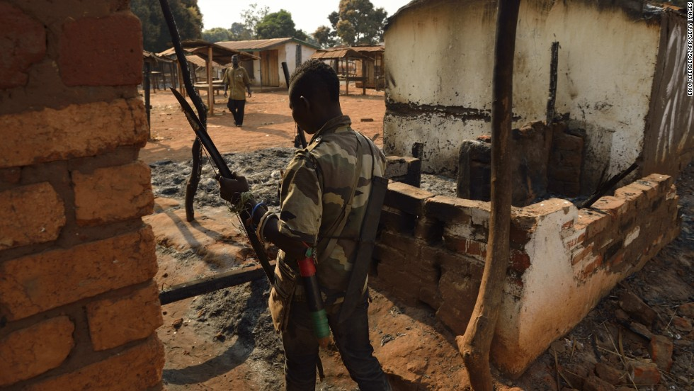 A Christian fighter walks by houses burned by ex-Seleka forces in Bogoura, a small town in the Central African Republic, on Sunday, January 19. The Seleka have been forced out of power since the coup, but Christian militias, known as the anti-balaka, have been allowed to fill the power vacuum, Amnesty International said, with dire consequences for Muslim civilians.