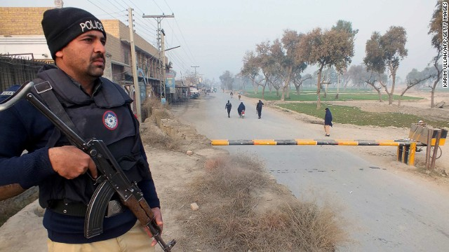 A Pakistani policeman stands guard near the site of a bomb attack on a security convoy in Bannu on January 19, 2014.