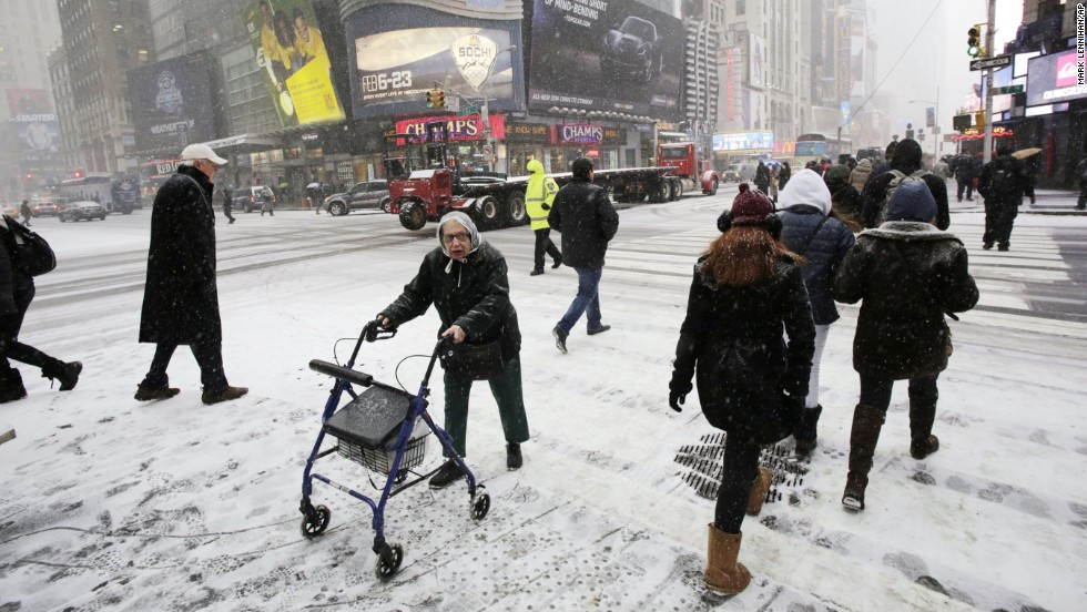Pedestrians make their way through snowfall in New York's Times Square on January 21.