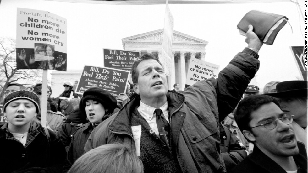 The Rev. Flip Benham, director of Operation Rescue National from Dallas, prays, sings and hoists his Bible over his head in front of the Supreme Court at the tail end of the March For Life march.