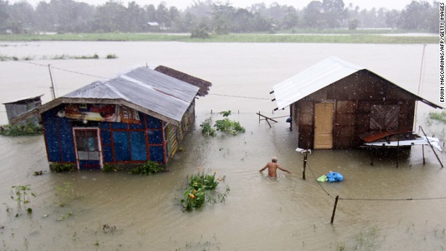 A resident of Butuan City on the southern Philippine island of Mindanao wades through floodwaters.