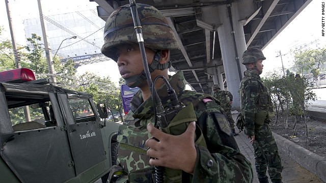 Thai soldiers stand guard at an intersection in Bangkok as the government calls a state of emergency