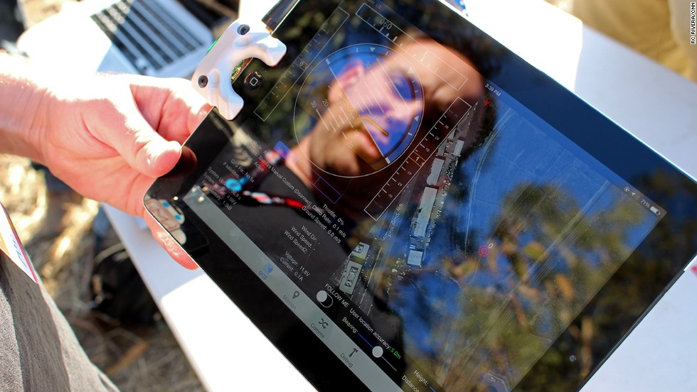 """<a href=""""http://www.fightingwalrus.com/"""" target=""""_blank"""">Fighting Walrus</a> co-founder Andy Brown demonstrates his company's iPad accessory (mounted on the left side of the tablet), a $129 device for controlling and communicating with drones."""