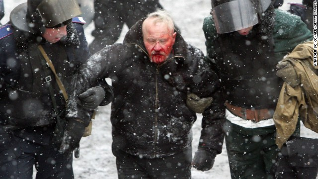 Ukrainian riot policemen detain a bleeding protester following clashes between security forces and pro-EU demonstrators in central Kiev on January 22, 2014. Five activists were killed and 300 wounded in the Ukrainian capital Kiev in a day of intense clashes with security forces, the medical centre of the protest movement said.