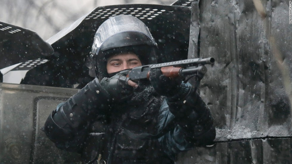 A police officer aims his shotgun during clashes with protesters.