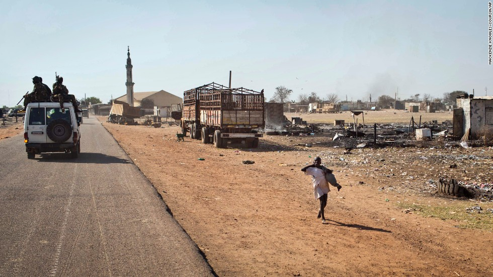 South Sudanese government forces riding on a vehicle through a still-smoldering town pass a boy after government forces retook the provincial capital of Bentiu on January 12.