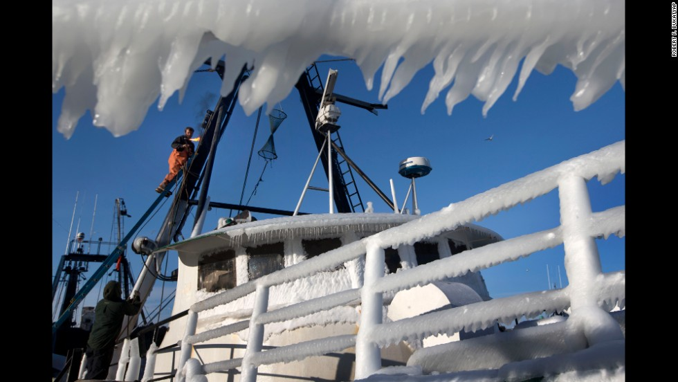 A fisherman fires up a welding torch while working on repairs to the Harmony, an ice-covered fishing trawler, in Portland, Maine, on January 23.