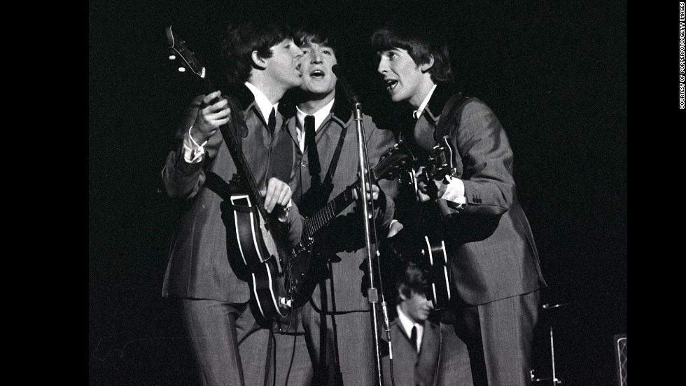 From left, McCartney, Lennon and Harrison share a microphone as they sing a song at Carnegie Hall.