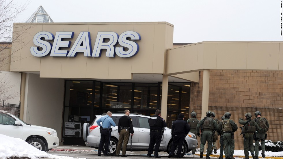 Police patrol outside a Sears store at the mall.